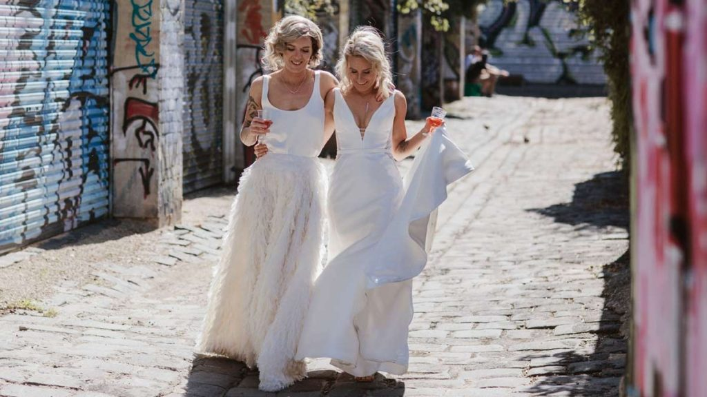 2 brides in recycled 2nd hand wedding dresses walking